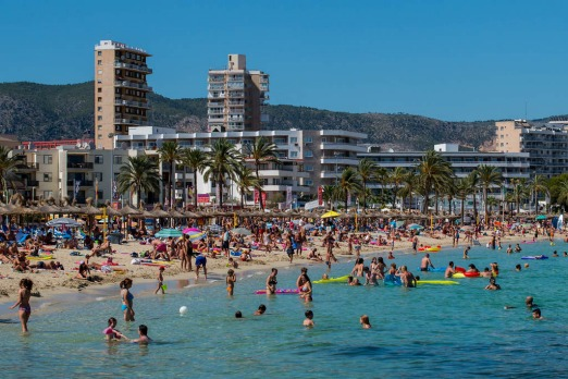 Tourists sunbathe at Magaluf beach in Mallorca, Spain.