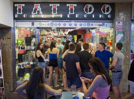 Young British tourists line up outside a tattoo shop of Punta Ballena street in the Magalluf zone, in Calvia on Mallorca ...