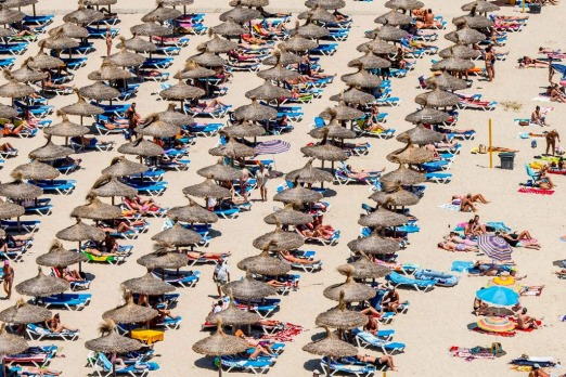 Tourist sunbathe at Magaluf beach in Mallorca, Spain.