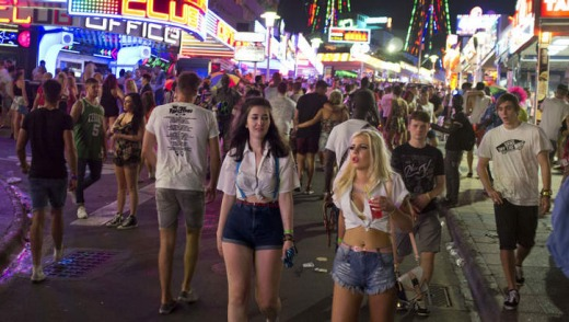 Young British tourists walk down Punta Ballena street as they have fun in the Magalluf zone, in Calvia on Mallorca Island.