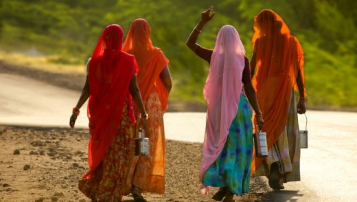 Four women wearing sari walking on dirt road in Rajasthan.