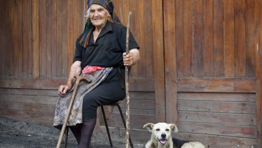 Peasant woman sitting on road with dog in Georgia.