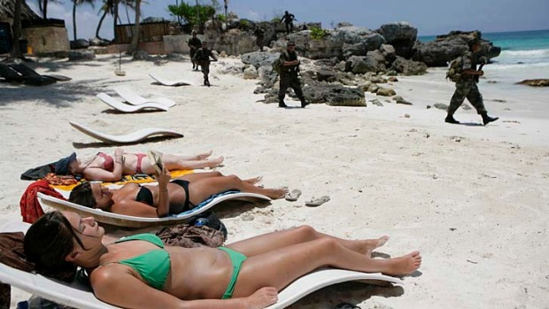 Travel bubble? No troubles. Soldiers pass sunbathing tourists in Mexico.