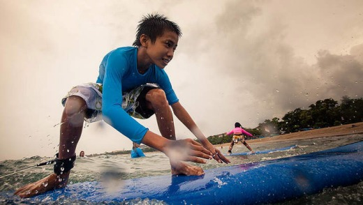A young boy catches a wave.