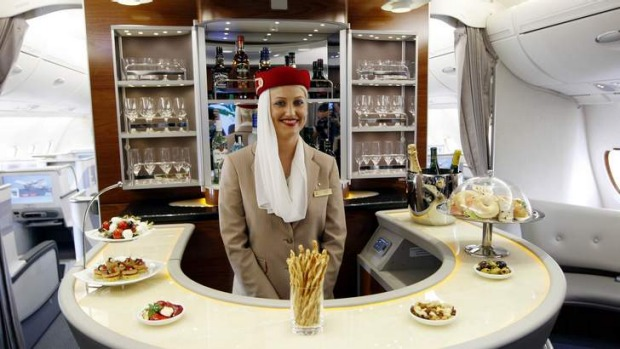 A flight attendant poses behind the bar in the rear of the business class section of Emirates' Airbus A380.