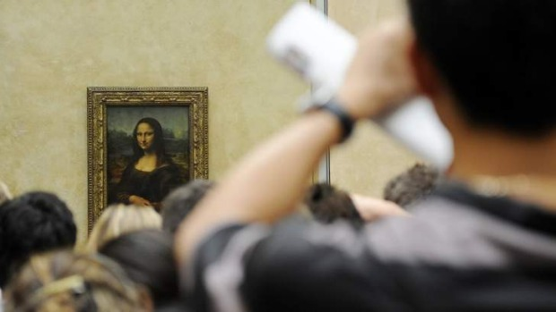A tourist takes souvenir photos of Italian painter Leonardo da Vinci's famed portrait Mona Lisa at the Louvre Museum in ...