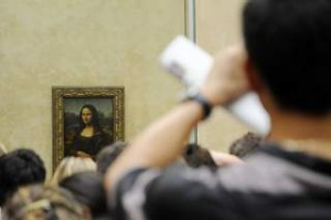 A tourist takes souvenir photos of Italian painter Leonardo da Vinci s famed portrait Mona Lisa at the Louvre Museum in ...
