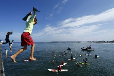 A group of junior lifeguards, the youngest at nine-years-old, take the plunge off a pier at Ocean Beach, California as part of their summer class and to help raise funds for the San Diego Junior Lifeguard Foundation.