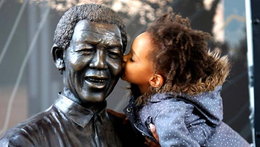 A young South African girl kisses a statue of the late South African president Nelson Mandela.
