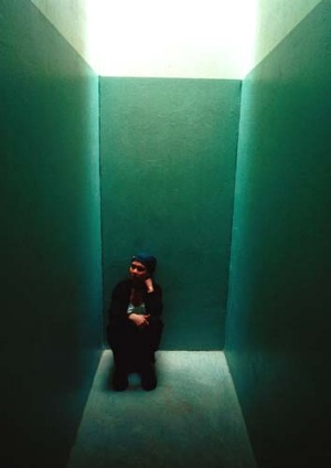Tour guide and former political prisoner Dawn Elliot sits in an isolation cell at the Apartheid Museum.
