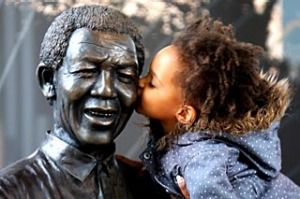 A young South African girl names Malika is lifted by her mother to kiss a statue of former South African President Nelson Mandela before a service conducted by Archbishop Desmond Tutu at the Nelson Mandela Foundation on December 9, 2013 in Johannesburg, South Africa.