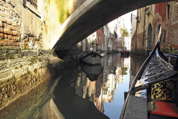 Gondola under a bridge in Venice.