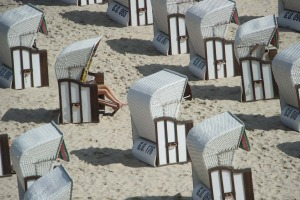 A woman sits in a beach chair on the beach in Sellin on the Baltic Sea island of Ruegen, northeastern Germany.