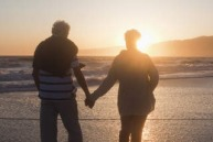Senior couple holding hands on beach at sunset