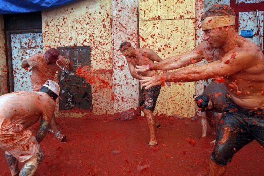 "Men throw tomatoes at each other, during the annual ""tomatina"" tomato fight fiesta in the village of Bunol. The streets ..."