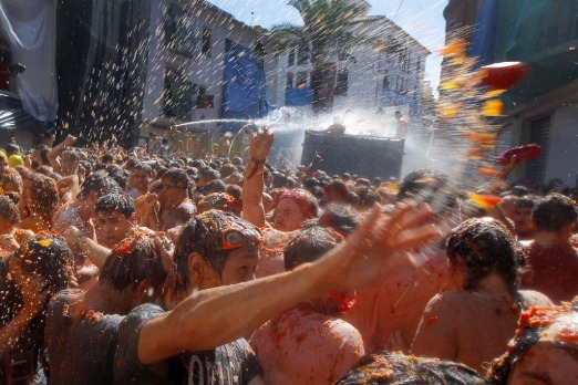 "Crowds of people throw tomatoes at each other during the annual ""tomatina"" tomato fight fiesta in the village of Bunol, ..."
