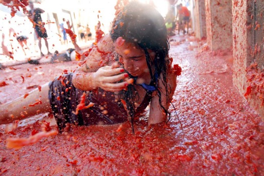 "A woman lays in a puddle of tomato juice during the annual ""tomatina"" tomato fight fiesta in the village of Bunol, 50 km ..."