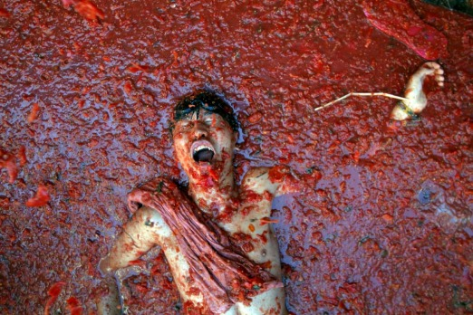 "A man lies in a puddle of squashed tomatoes, during the annual ""tomatina"" tomato fight fiesta in the village of Bunol, ..."