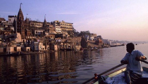 A boatman at dawn on the Ganges River beside the holy city of Varanasi in India.