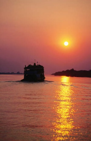 A passing ferry at sunset on Irrawaddy River, Myanmar.