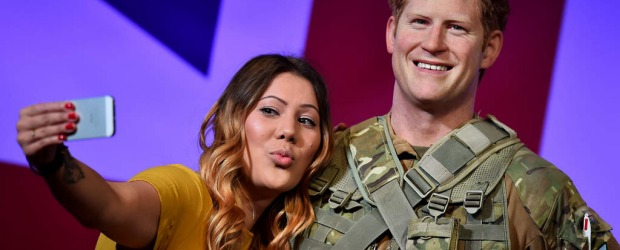 A woman poses for pictures as she takes a selfie with a new wax figure of Britain's Prince Harry dressed in army fatigues at Madame Tussauds in central London. Prince Harry will celebrate his 30th birthday on September 15.