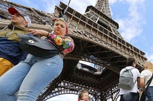Tourists walk near the Eiffel Tower in Paris.