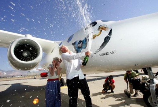"Virgin Galactic founder Sir Richard Branson, right, celebrates the naming of mothership aircraft White Knight Two ""Eve"" ..."