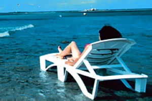 WOMAN LYING ON BEACH CHAIr.