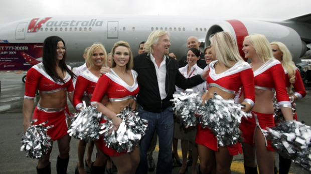 Sir Richard Branson, chairman of Virgin Group, poses for photos with local promotional models in cheerleading uniforms ...