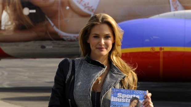 Bar Refaeli holds the 2009 cover of Sports Illustrated (SI) swimsuit issue, as she unveils SI One, a Southwest Airlines Boeing 737-700 wrapped with her image.