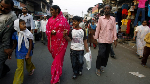 Street life ... Slumdog Millionaire star Azharuddin Ismail (white T-shirt) walks with his family near a Mumbai slum.