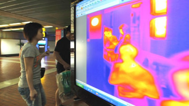 Passengers go through a thermal scanner at Jakarta's international airport. Thermal scanners will be used at eight Australian international airports from today.