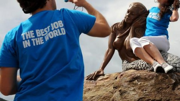 'Best Job In The World' finalist James Hill (L) of Australia takes a photo of Mirjam Novak (R) of Germany on a mermaid sculpture on Daydream Island in the Whitsunday Islands.