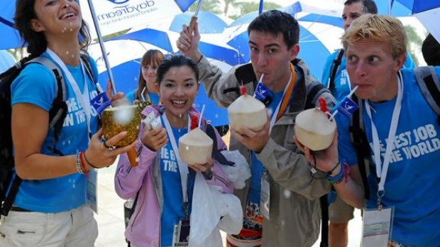 The 'Best Job In The World' finalists (L to R) Magali Heuberger (The Netherlands), Mieko Kobayashi (Japan), Ben Henry (France) and Ben Southall (UK) sip pina coladas from coconuts and a pineapple during a tropical downpour on Daydream Island in the Whitsunday Islands.