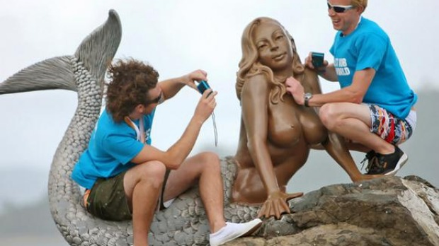 """The Best Job in the World"" competition finalists George Karellas (L) of Ireland and Ben Southall of Britain sit on a mermaid statue during a media opportunity on Daydream Island, about 950km (590 miles) north of Brisbane."
