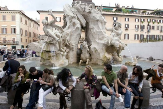 "Romans sit by the side of Giovanni Lorenzo Bernini's sculpture Fontana dei Quattro Fiumi (""Fountain of the Four Rivers"")."