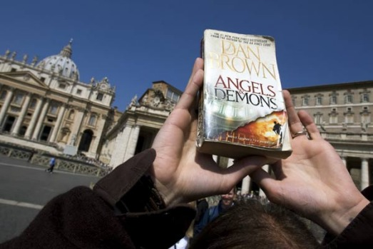"A guide with the ""Official Angels & Demons Tour"" holds a copy of the book by Dan Brown while accompanying a group of ..."