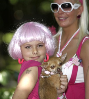 "A girl poses with her dog during the ""Go Blonde!"" fundraising charity event in Riga."