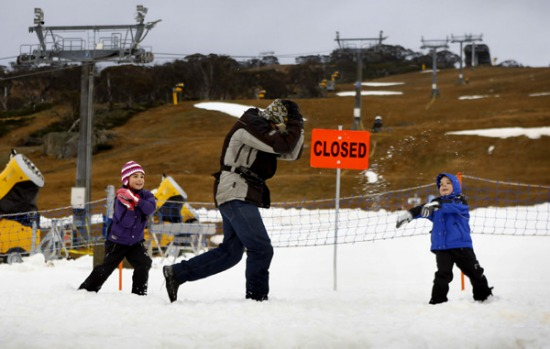 Angelina, six, and Michael Gialamas, four, of Abbotsbury attack Roger Carrothers of Avalon with snowballs at Perisher.