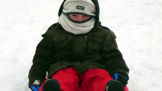 A young tobogganer tries out the snow at Mount Buller.