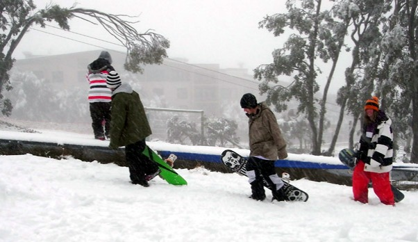 Snowboarders head up Mount Buller's Bourke Street.
