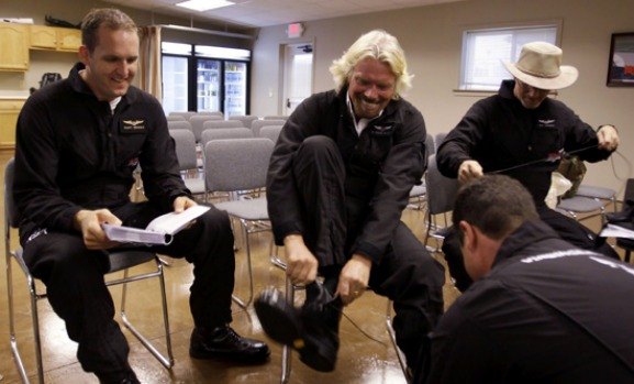 Richard Branson puts on flight boots during preflight training to fly on WhiteKnightTwo.