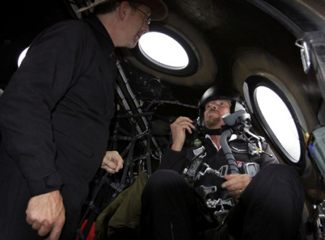 Richard Branson listens to preflight instructions from Lead Project Engineer Bob Morgan as he prepares to fly on Virgin ...