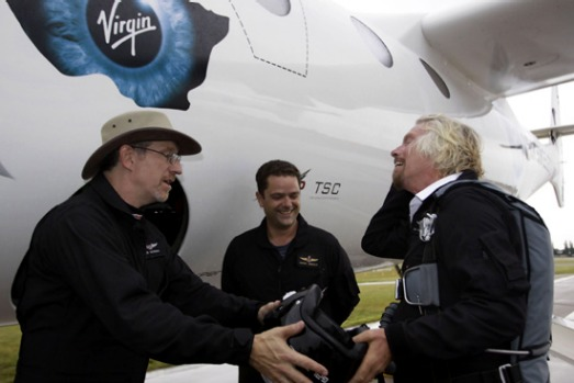 Richard Branson hands his helmet to Lead Project Engineer Bob Morgan with Pilot Pete Siebold looking on after preparing ...