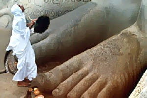 Piety prevails ... a Jain pilgrim prays at the feet of the statue of Gommateshwara.