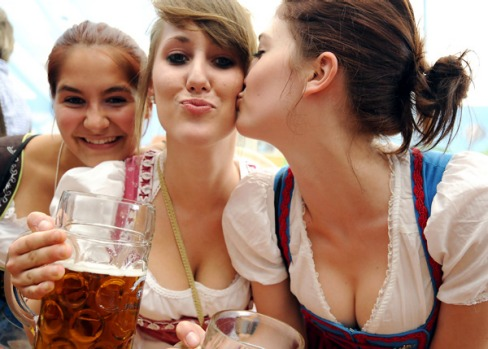 Young women in dirndl dresses pose with beer mugs at the Oktoberfest.