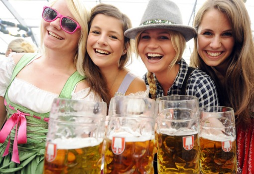 Young women in traditional bavarian dresses pose with beer mugs at the Oktoberfest.
