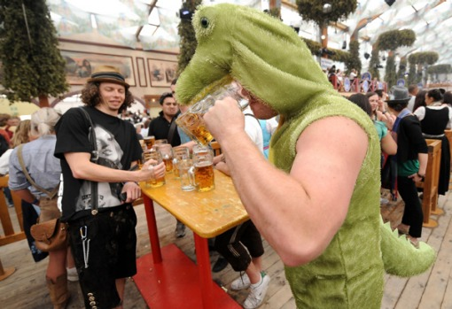 A man wearing a dragon costume drinks beer at the Oktoberfest beer festival.