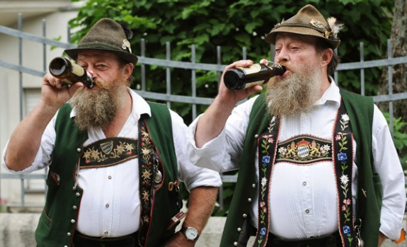 German twin brothers in traditional clothes drink a beer as they watch the marksmen's parade.
