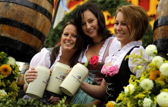 Waitresses hold their beer mugs as they arrive in a parade for the opening of the traditional Bavarian beer festival ...